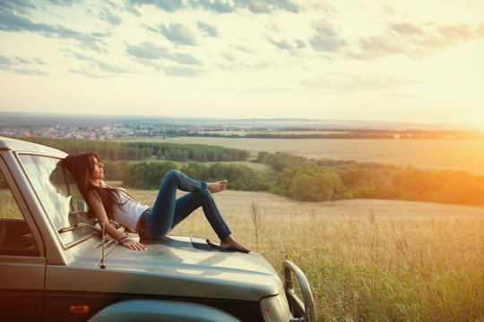 Attractive yong woman is lying on the car's hood and looking at sunset. Rural evening background.