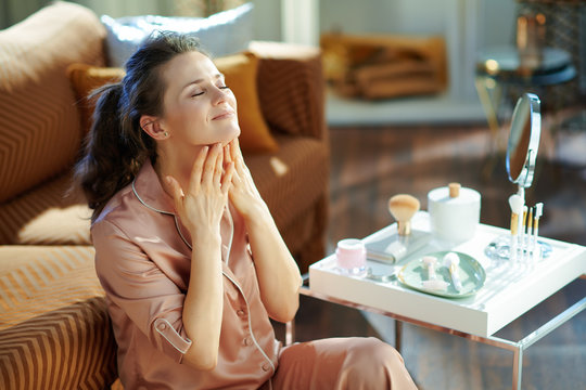 woman applying neck cream at modern home in sunny winter day