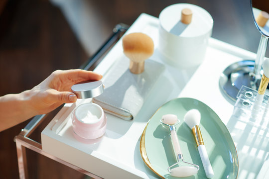 stylish woman opening jar on table with toiletries