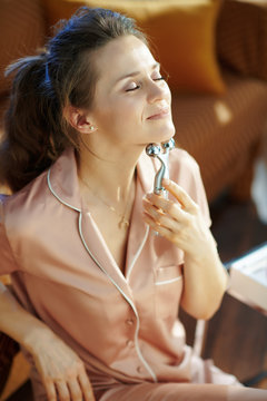 woman in modern living room in sunny winter day using massager