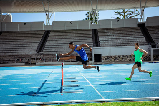 Athletes jumping over a hedge at the stadium
