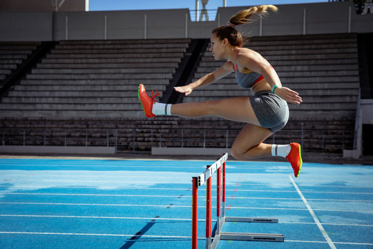 Athlete jumping over a hedge at the stadium