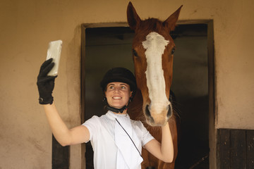 Caucasian woman taking selfies with her dressage horse