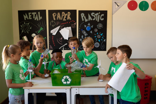 Group of schoolchildren wearing green t shirts with a white recycling logo on them standing around a