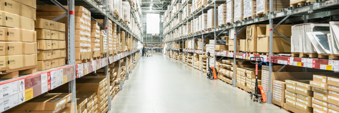 Panorama of Rows of shelves with boxes in modern warehouse