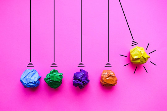 Crumpled paper pendulum on pink background - Idea Concept Background