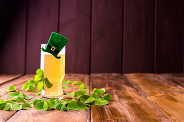 A glass of frothy beer with decor and fresh clover leaves. Drink on a wooden background. Concept of images for the traditional holiday of St. Patrick's Day. Copy space.
