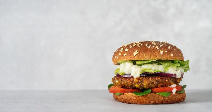 Vegan lentils burger with vegetables on light gray background