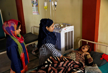 Shabana Parveen reacts after a medic tends to her at Al Hind hospital after she and her family fled their home following clashes between people demonstrating for and against a new citizenship law in a riot affected area in New Delhi