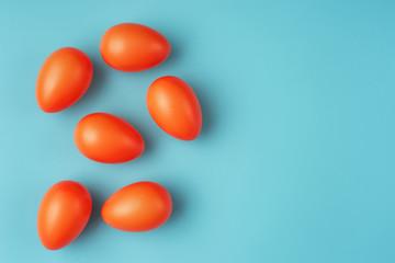 Close up of vivid orange Easter eggs on blue-green background