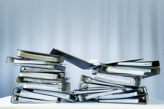 heap of ring binder with files, folders and documents on an office desk, showing much business work, gray curtain background with copy space