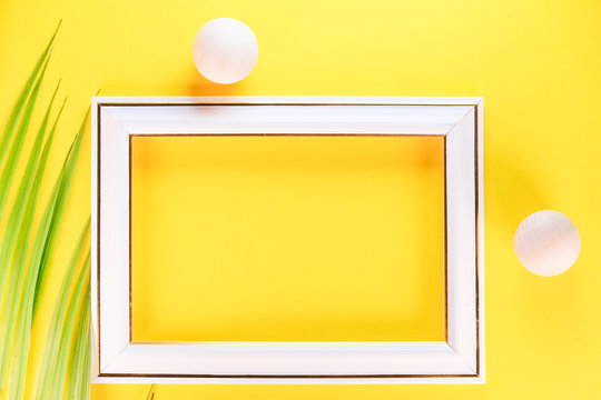 image of a photo frame on a yellow background framed by wooden balls