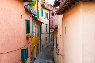 Zelfklevend Fotobehang Smal steegje High angle aerial view on Chiusi, Italy street narrow alley in small historic town village in Umbria on sunny day with orange yellow bright vibrant colorful walls, windows shutters