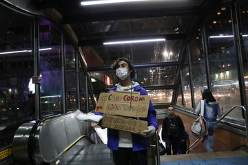 """Student Gabriel Prodoscimo de Araujo, 18, sells masks while wearing a placard that reads, """"First corona case confirmed - prevent yourself, wear a mask"""" at a subway station in Sao Paulo"""