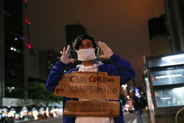 """Student Gabriel Prodoscimo de Araujo, 18, poses for a photo as he sells masks while wearing a placard that reads, """"First corona case confirmed - prevent yourself, wear a mask"""" at a subway station in Sao Paulo"""