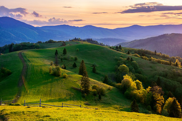 mountainous countryside in springtime at dusk. road, wooden fence and trees on the rolling hills. ridge in the distance. clouds on the sky. beautiful rural landscape of carpathians