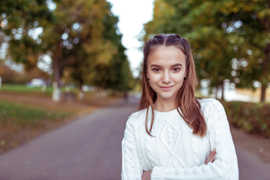 Portrait of a teenage girl of 12 years old, in summer in park, casual clothes, white knitted sweater, free space for copy text. Weekend break. Emotions of happiness are smiles and positive.