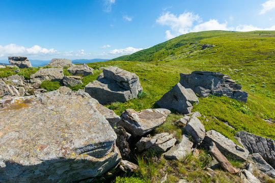 rocks on the alpine hillside meadow. beautiful summer nature scenery. green grass on the hills and fluffy clouds on the blue sky. stunning mountain landscape of carpathians
