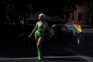 A participant dances in the street with a rainbow pride flag before the 42nd anniversary of the Sydney Gay and Lesbian Mardi Gras Parade in Sydney