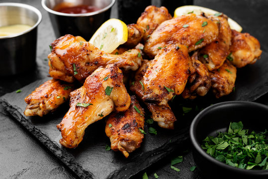 Baked chicken wings served with different sauces and lemon. Black background