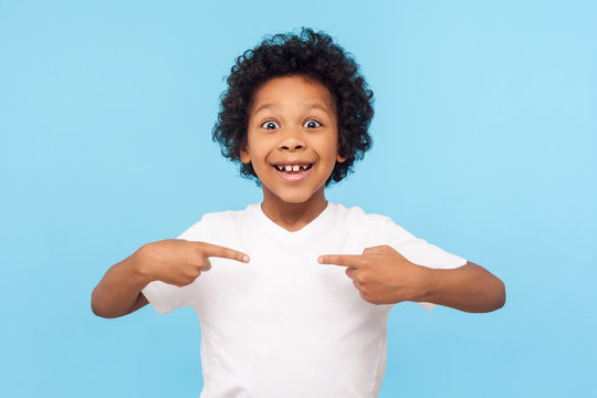 Wow, this is me! Portrait of amazed happy preschool boy in T-shirt looking at camera with shocked face and pointing himself, being proud and surprised. indoor studio shot isolated on blue background