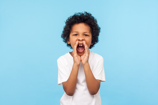 Attention! Portrait of little boy with curly hair in white T-shirt holding hands near wide open mouth and shouting loudly, screaming announcement. indoor studio shot isolated on blue background
