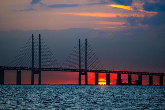 Oresund Bridge between Denmark and Sweden, Oresundsbron. Sunset landscape view whit passing ship under the bridge. Malmo to Copenhagen.