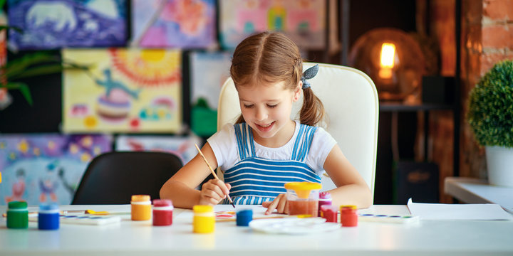 funny child girl draws laughing   with paint.