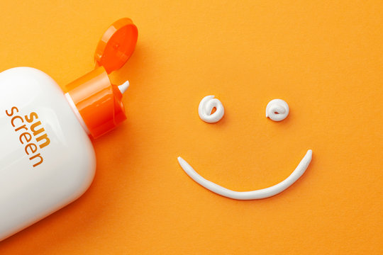 Sunscreen on orange background. Plastic bottle of sun protection and white cream in the shape of Smiley, smiling face