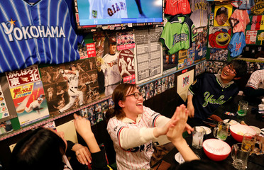 "Baseball fans react as they watch live on TV the preseason of the baseball game of Yomiuri Giants and Tokyo Yakult Swallows at a Baseball-themed traditional Japanese ""Izakaya"" pub, Lilies Kanda Stadium, in Tokyo"