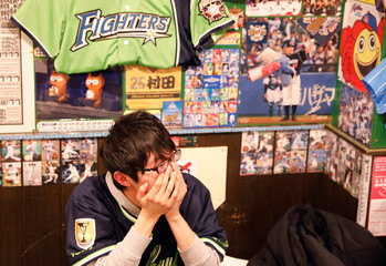 "A baseball fan reacts as he watches live on TV the preseason of the baseball game of Yomiuri Giants and Tokyo Yakult Swallows at a Baseball-themed traditional Japanese ""Izakaya"" pub, Lilies Kanda Stadium, in Tokyo"