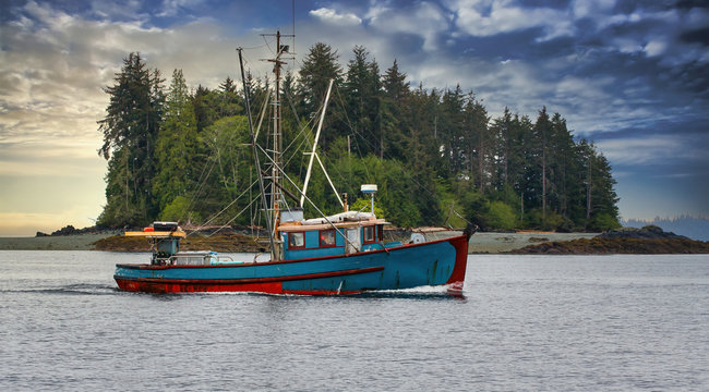 A blue shrimp boat trolling the grey waters of Alaska