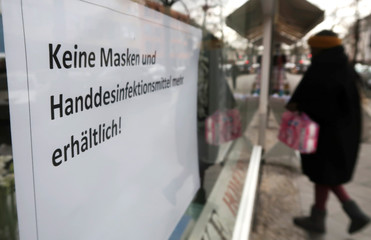 A sign written in German announcing that protective masks and hand sanitiser are sold out is seen at a pharmacy in Berlin