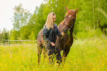 Smiling woman feeding her arabian horse with snacks in the field