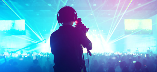 social media concept cameraman with crowd people  exitied moment in colorful lighting concert event with abstract blur bokeh background