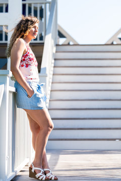 Seaside white boardwalk walkway steps by ocean with young woman girl leaning back on railing in Florida architecture view during sunny day