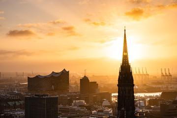 The sun shines through the church tower of St. Nikolai church in the city centre of Hamburg, Hamburg, Germany