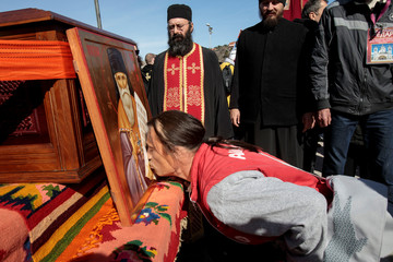 An Orthodox believer kisses an icon next to the relics of St Simeon before a protest march against a new law on religious freedom and legal rights of religious organizations, in Podgorica