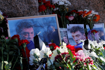 Flowers and photographs of Russian opposition politician Boris Nemtsov are placed at the Solovetsky Stone memorial during a rally marking the 5th anniversary of his murder, in Saint Petersburg
