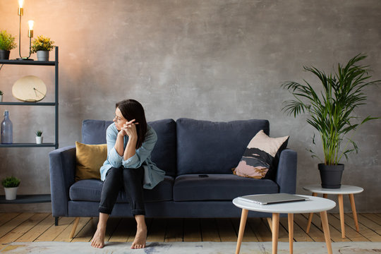 Worried woman sitting on couch at home. Frustrated confused female feels unhappy, problems in personal life, quarrel break up with boyfriend and unexpected pregnancy concept