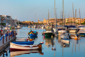 Wall Mural - Valletta harbour with yachts and multicolored fishing boats Luzzu with eyes, church and fortress, illuminated by sunset light, Malta