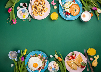 Easter breakfast flat lay with scrambled eggs bagels, tulips, pancakes, bread toast with fried egg...