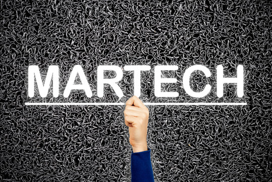 Woman showing MARTECH sign, on wire dark background. Martech is the blending of marketing and technology.