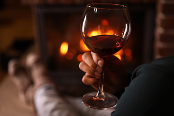 Spoed Foto op Canvas Wijn Man with glass of wine near fireplace at home, closeup