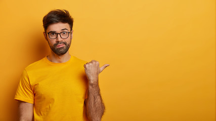 Photo of wondered bearded man points thumb right on copy space, shows amazing sale discount, demonstrates shopping offer, wears glasses and yellow casual t shirt, has worried expression, poses indoor