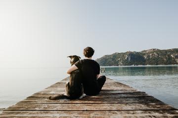 Mensch umarmt Hund auf einem Steg mit Blick auf einen wunderschönen See mit Bergen