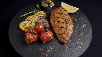 Fototapete - grilled chicken fillet with vegetables black background rotation 360 degrees. 4K