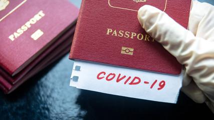Coronavirus and travel concept. Note COVID-19 coronavirus and passport. Novel corona virus...