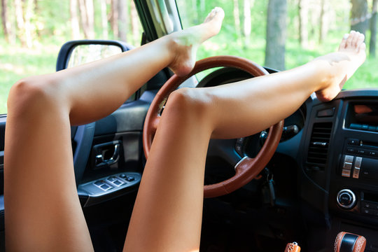 Sexy female legs with smooth skin on a dashboard of a car