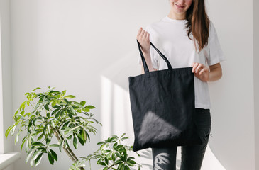 Young woman holding black textile eco bag againstwhite wall. Ecology or environment protection concept. White eco bag for mock up.